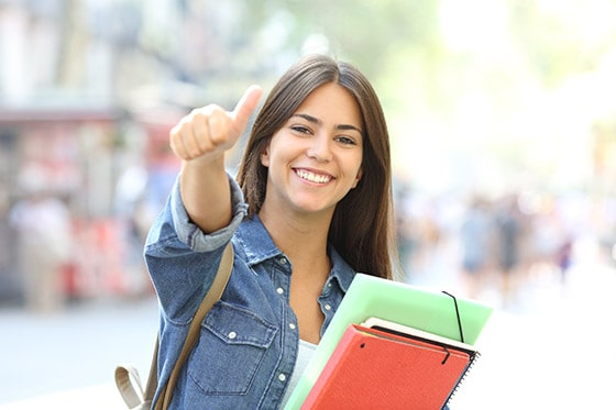 Female student smiling and giving a thumbs-up. Take Note students show tangible and significant improvement on tests such as the ACT and SAT.